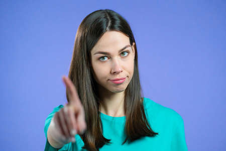 Portrait of serious woman showing rejecting gesture by stop finger sign. Girl isolated on violet background.