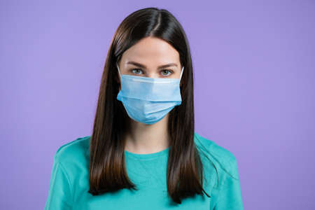 Woman in medical protective mask . Girl on violet studio background. Coronavirus concept.