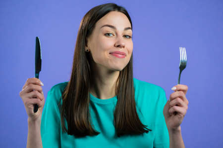 Portrait of hungry woman with fork and knife. Lady waiting for serving dinner dishes with cutlery on violet studio background.