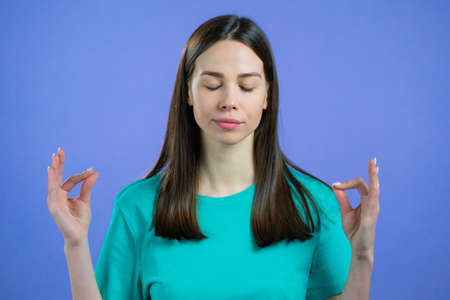 Calm woman relaxing, meditating. She calms down, breathes deeply with mudra om on violet studio background. Yoga concept. Stockfoto