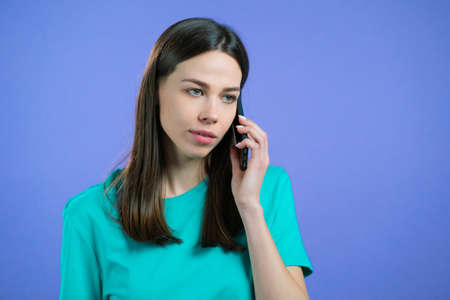 Young woman speaks with smile on phone. Girl holding and using smart phone. Violet studio background.