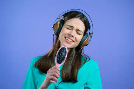 European woman singing and dancing with hair brush or comb instead microphone at violet studio background. Lady in headphones having fun, listening to music, dreams of being celebrity.