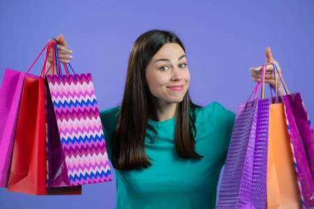 Excited woman with colorful paper bags after shopping on violet studio background. Concept of seasonal sale, purchases, spending money on gifts