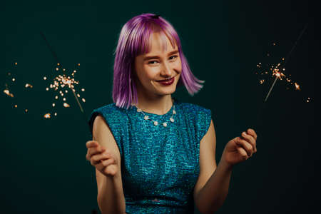 Hipster woman with sparkling bengal fire on green background. Christmas holiday concept. Young dyed violet haired girl with sparkler celebrating, smiling, enjoying time.