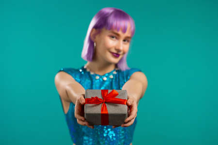 Woman with violet hair gives gift box by hands to camera on blue studio background. Girl smiling, she is happy with present.