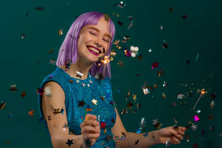 Hipster woman with sparkling bengal fire dancing under confetti rain on green background. Christmas holiday concept. Young dyed violet haired girl with sparkler celebrating, smiling, enjoying time. Stockfoto