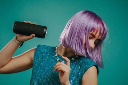 Trendy woman with dyed purple hair listening to music by wireless portable speaker - modern sound system. Young lady dancing, enjoying on turquoise studio background
