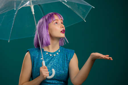 Unusual violet haired woman stands under umbrella blue in studio. Concept of fashionable girl, hipster lifestyle, trendy outfit,
