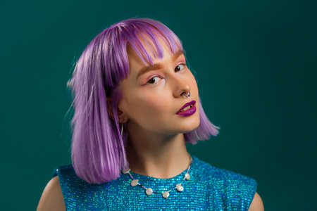 Portrait of hipster woman with dyed violet hair over turquoise studio background. Positive young party girl looking to camera. Amazing sparkling outfit