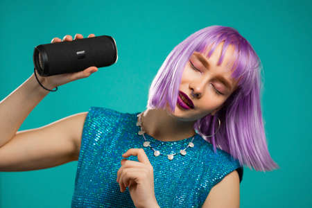 Unusual woman with dyed violet hairstyle listening to music by wireless portable speaker - modern sound system. Young girl dancing, enjoying on turquoise studio background