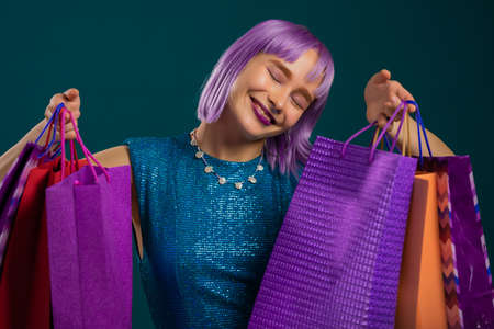 Excited violet haired woman with colorful paper bags after shopping on studio background. Concept of seasonal sale, purchases, spending money on gifts