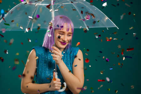 Unusual violet haired woman stands under umbrella, rejoices over confetti rain in studio. Concept of fashionable girl, wow idea, celebrating, party, winning