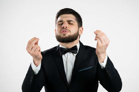 Young man making delicious, perfect gesture. gentleman with beard in tuxedo admires taste of italian food on white studio background. Bellissimo concept.