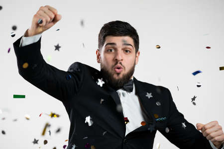 Excited elegant man having fun, screaming WOW, rejoices over confetti rain in studio. Guy in black tuxedo suit with bowtie. Showman. Concept of celebrating, birthday party, winning