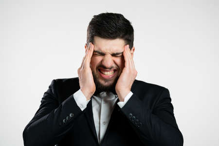 Young man having headache, studio portrait. Guy in tuxedo putting hands on head, isolated on white background. Concept of problems, medicine, illness Stock fotó