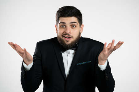 Indifferent unsure man in tuxedo makes gesture of I dont know, cant help anything. Difficult question concept. Guy with beard on white studio background.