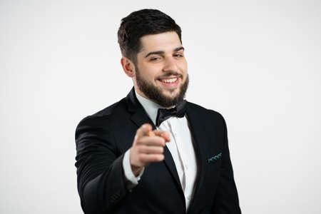 Charming man in tuxedo points index finger into camera lens and winks, flirts. Hey, you. Guy with beard in holiday festive suit on white background. Stock fotó