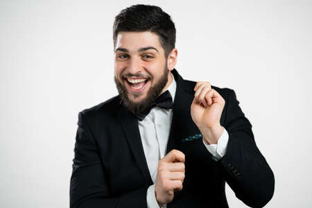 Bearded man in tuxedo dancing positive on white studio background. Handsome male model showman. Party, happiness, occupation concept.