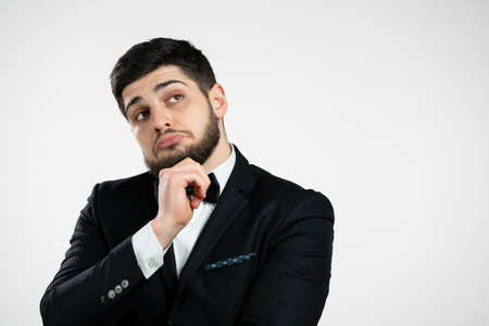 Thinking man looking up on white background. Pensive face expressions. Handsome bearded man in black tuxedo