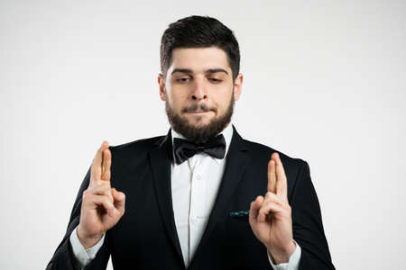 Young caucasian man praying with crossing fingers over white background. Guy in black tuxedo begging someone satisfy his desires, help with.