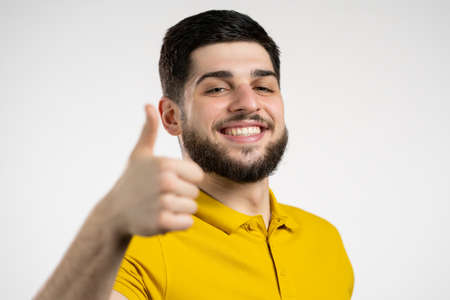 Handsome man in yellow wear shows thumb up Like gesture. Happy guy on white background. Winner. Success. Positive male model smiles to camera. Body language. Stock fotó