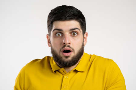 Frightened man afraid of something and looks into camera with big eyes full of horror over white wall background.