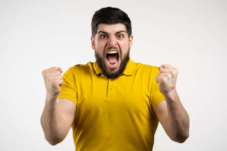 Angry stressed man shouting isolated over white background. Depressed guy loudly screaming in rage to camera.