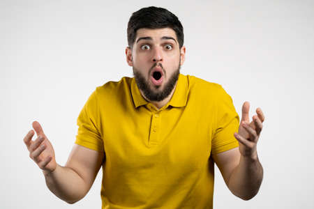 Man depicts amazement, shows WOW delight face effect. Surprised excited happy guy in yellow wear. Handsome male shocked model on white background.