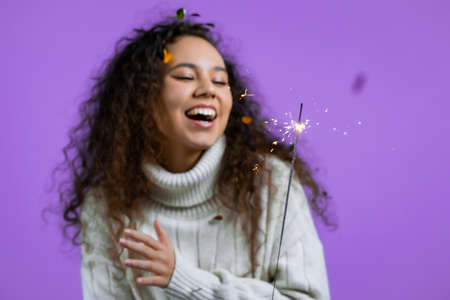 Curly woman with sparkling bengal fire dancing on violet background. Christmas holiday concept. Young girl with sparkler celebrating, smiling, enjoying time. Stock fotó