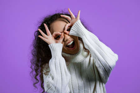Positive girl making OK sign over eyes like glasses on purple background and smiles to camera. Body language. Young woman.