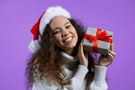 Beautiful woman in Santa hat received gift box with bow. She is happy and flattered by attention. Girl in sweater smiling with present on purple background. New year, Christmas concept. Stock fotó