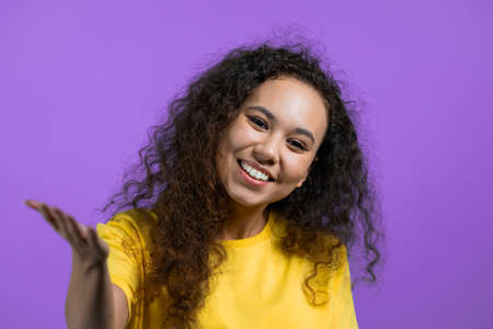 Beautiful woman showing - Hey you, come here. Girl in yellow ask join her, beckons with inviting hand hugs gesture. Lady is looking playful flirtatious, inviting to come. Violet studio background. Stock fotó