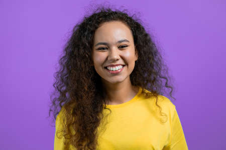 Portrait of pretty woman over violet studio background. Positive young girl with natural curly hair smiles to camera.
