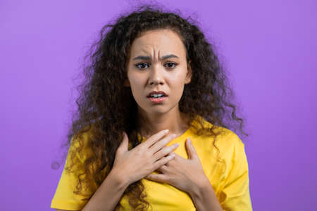 Unpleasantly surprised and shocked girl on violet studio background. Woman received bad news. She expresses sympathy and regret. Stock fotó