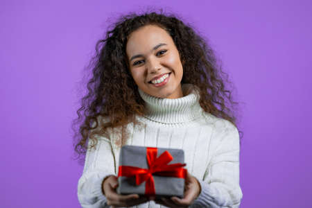 Woman with curly hair gives gift box by hands to camera on purple studio background. Girl smiling, she is happy with present.