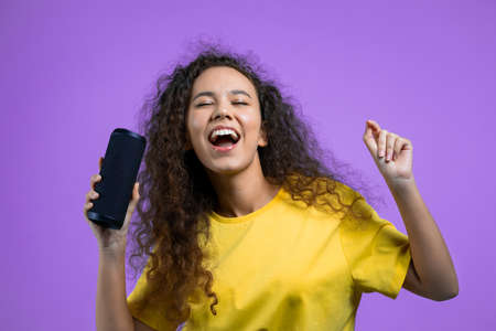 Mixed race woman listening to music by wireless portable speaker - modern sound system. Teenager dancing, enjoying on violet studio background. She moves to the rhythm of music.
