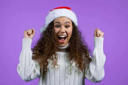 Woman in Santa hat is very glad and happy, she shows yes gesture of victory, she achieved result, goals. Surprised excited happy lady on violet studio background. New year, Christmas concept.