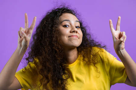 Pretty woman with curly hair showing with hands and two fingers air quotes gesture, bend fingers isolated over violet background. Not funny, irony and sarcasm concept.