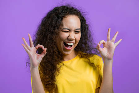 Pretty woman showing ok, okay sign over purple studio background. Positive young girl with natural curly hair smiles to camera. Winner. Success. Body language.