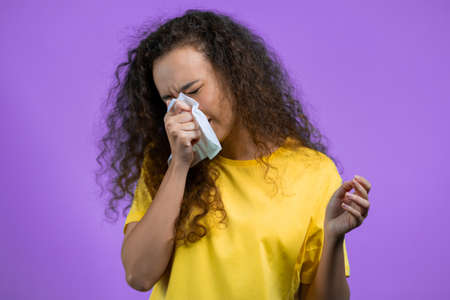 Pretty woman sneezes into tissue. Isolated girl on purple studio background. Lady is sick, has a cold or allergic reaction. Coronavirus, epidemic 2021, illness concept Stock fotó