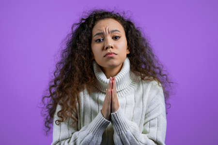 Beautiful woman praying over purple background. Girl in white sweater begging someone to satisfy her desires, help with.