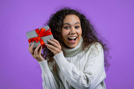 Beautiful woman in sweater received gift box with bow. She is happy and flattered by attention. Girl in sweater smiling with present on purple background. New year, Christmas concept.