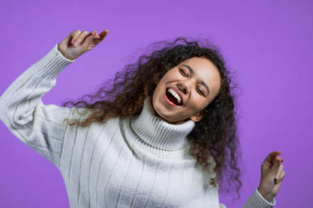 Attractive woman with curly hairstyle dancing on purple studio background. Girl in white winter sweater. Positive mood.