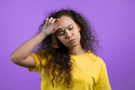 Portrait of woman having headache, purple studio portrait. Girl putting hands on head. Concept of migraine problems, medicine, illness