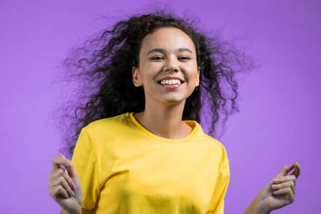 Portrait of cute woman on purple background. Positive young girl with waving natural curly hair, she smiles to camera.