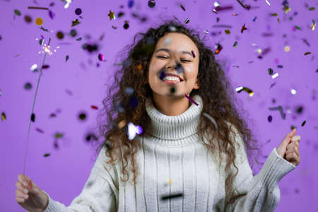 Curly woman with sparkling bengal fire dancing under confetti rain on violet background. Christmas holiday concept. Young girl with sparkler celebrating, smiling, enjoying time.
