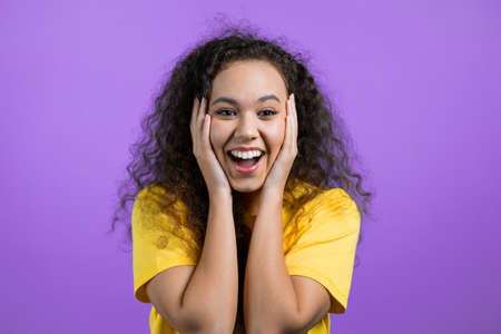 Mixed race woman is very glad, she screaming loud. Concept of sales, profitable offer. Excited happy lady on purple studio background.