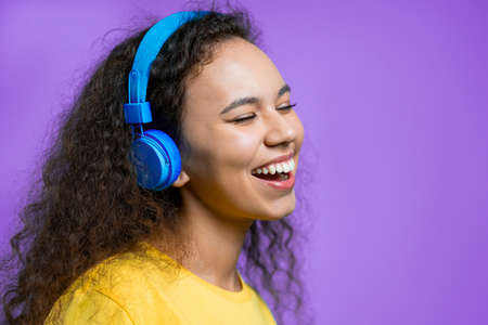 Attractive woman dancing with wireless headphones on violet studio background. Cute girl dancing and smiling. Music, radio, happiness, freedom, youth concept.