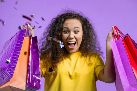 Excited woman with colorful paper bags after shopping on violet studio background. Confetti rain. Concept of seasonal sale, purchases, spending money on gifts