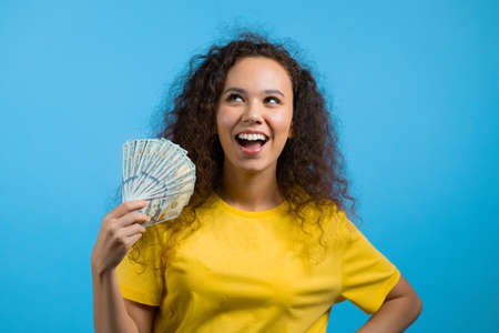 Mixed race woman with cash money - USD currency dollars banknotes on blue background. Symbol of jackpot, salary, winning the lottery